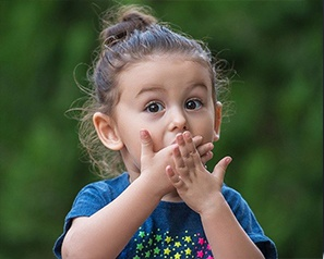 Little girl with toothache covering her mouth