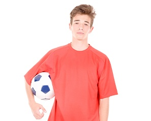 Teen with knocked out tooth holding a soccer ball