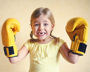 Little girl with knocked out front teeth wearing boxing gloves