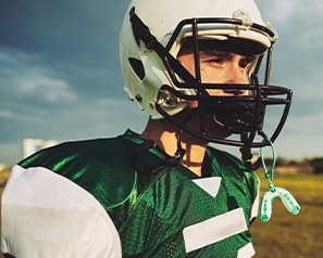 Teen wearing football helmet with potentially fractured jaw