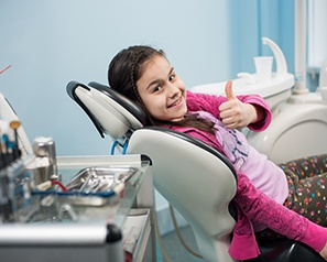 A young girl lying back in a dentist's chair and giving a thumbs up after seeing her dentist about a dental emergency