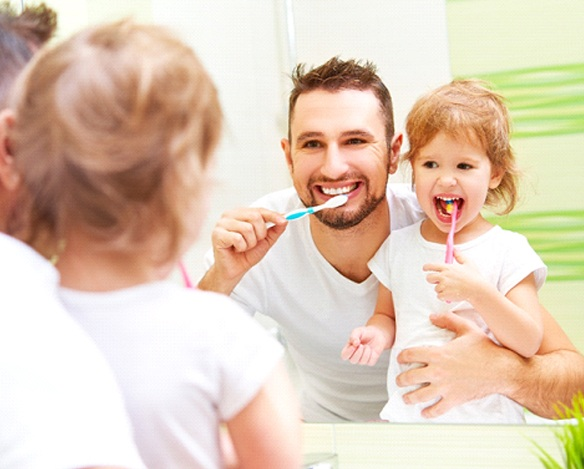 A father and daughter brushing their teeth while standing in front of the mirror in their bathroom