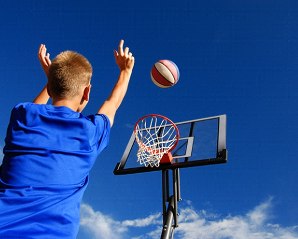 A male teenager shooting a basketball into a hoop on a court