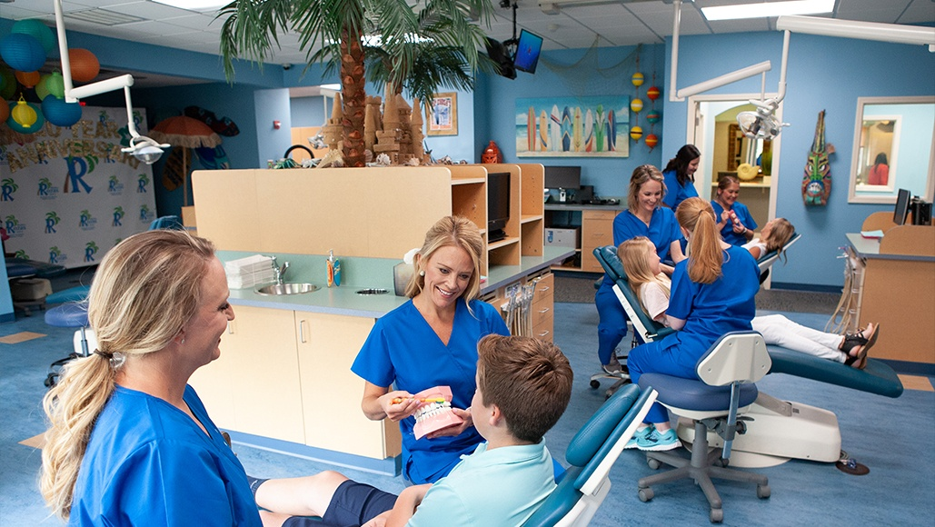Team members helping young patients at a room of dental chairs