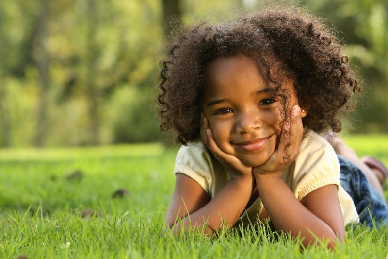 a little girl laying in the grass and holding her face between her hands while smiling