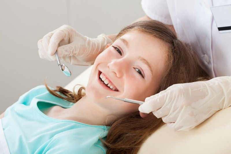 a little girl smiling at her dentist during a regular checkup